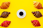 Coffee and croissants on yellow background top view