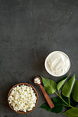 Cottage cheese in wooden bowl on black table top view copy space
