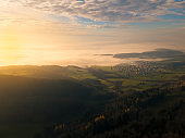 sunrise over switzerland from the jura mountains onto the flat land with fog and the community of günsberg