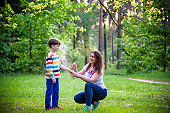 Young woman mother applying insect repellent to her son before forest hike beautiful summer day or evening. Protecting children from biting insects at summer. Active leisure with kids.
