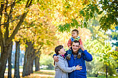 Family of three walks in the autumn park holding hands. happy father carrying son with maple leaves. Mother embrace her cute boy child. Happy family leisure together concept