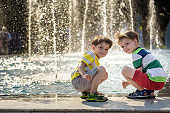 Cute toddler boy and older brothers, playing on a jet fountains with water splashing around, summertime