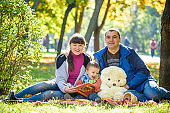 happy family enjoying autumn picnic. Father mother and son sit on field with apples basket teddy bear and reading book. Happy family leisure together concept