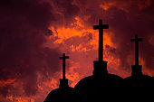 Catholic crosses silhouette with a darkness's sunset background. We live in dangerous times, this Easter stay home and pray for the coronavirus victims all over the world.