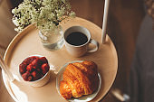 Breakfast on a tray in bed at home white dark linen. croissant tea strawberries