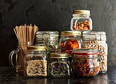 Food set. Raw cereals, pasta, groats, organic legumes and useful seeds in glass jars.