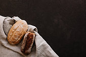 Various crispy bread and buns on the stone table, Loaf of fresh baked artisan sliced rye bread over dark texture background. Top view, copy space