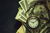 Vintage pocket watch on dollar banknote. At 8 o'2019clock in morning.