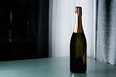 Elegant champagne bottle standing on glass table. Drink, alcohol, advertisement and holidays concept.