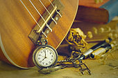 An antique pocket watch leaned against a ukulele and old book with vintage map and brass pen placed on wooden table.