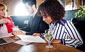 Young black woman reading documents on business meeting in restaurant