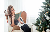 Young beautiful woman relaxing reading book sitting next to Christmas tree