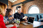 Couple talking with agent using laptop about the offer in the restaurant, business talk