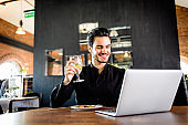 Successful handsome businessman eating and using laptop at restaurant