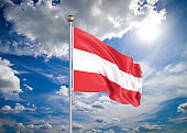Realistic flag. 3D illustration. Colored waving flag of Austria on sunny blue sky background.
