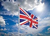 Realistic flag. 3D illustration. Colored waving flag of United Kingdom on sunny blue sky background.