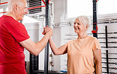 Senior people at the gym giving highfive after training