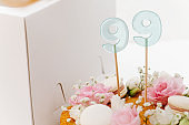 Close up image of honey cake with flowers and macarons next to a box