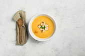 Pumpkin and carrot soup with cream and spinach with crackers on a white background.