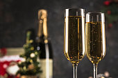 New year 2021 - two glasses of champagne on a dark background with bokeh from garlands.