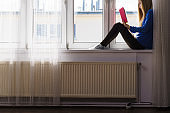 Woman sitting on window sill reading book at home