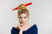 Thinking blonde woman having big pencil in hair