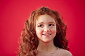 Portrait Of Girl With Long Red Hair Against Red Studio Background Smiling At Camera