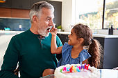Granddaughter Celebrates Birthday With Grandfather By Putting Cake Cream On His Nose And Laughing