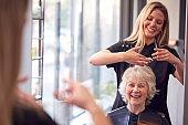 Senior Woman Having Hair Cut By Female Stylist In Hairdressing Salon