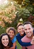 Portrait Of Smiling Hispanic Family With Parents Giving Children Piggyback Rides In Garden At Home