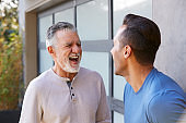 Senior Hispanic Man Talking And Laughing With Adult Son In Garden At Home