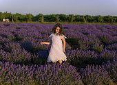 Cheerful pretty little girl in pink dress in a lavender field at the sunset background.