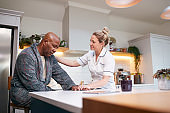 Depressed Mature Man In Dressing Gown Talking With Female Nurse In Kitchen At Home