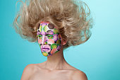 Profile portrait of a female model with colored face painted and ruffled hairstyle. Art beauty image.