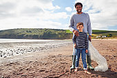 Portrait Of Father And Son Collecting Litter On Winter Beach Clean Up