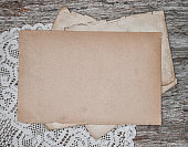 Old retro paper sheet with lace on the vintage rustic wooden board