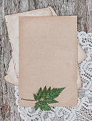 Old retro page sheet with lace and dry plant on the vintage rustic wooden board
