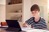 Boy Sitting At Kitchen Counter Doing Homework Using Digital Tablet