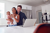 Portrait Of Family With Baby Daughter In Kitchen Using Laptop On Counter