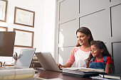 Hispanic Mother And Daughter Using Laptop In Home Office Together