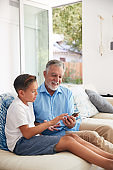 Hispanic Grandson Showing Grandfather How To Use Mobile Phone At Home