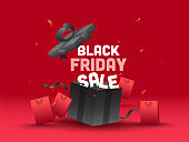 Black Friday Sale Text with Open Realistic Gift Box and Shopping Bags on Red Background for Advertising.