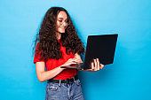 Young beautiful girl using laptop isolated on blue background