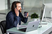 Smiling young call center man operator in headset working with laptop in office