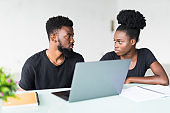 Two young african coworkers working together in a modern office. African black business partners using laptop and discussing new startup project.