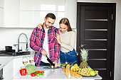 Young beautiful couple in kitchen. Family of two preparing food. Couple making delicious fresh salad.
