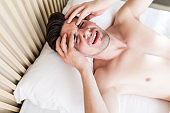 Handsome man wake up with head pain suffers from headache in his bed