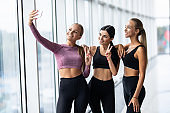 Selfie time, girls. Three girlfriends in fashionable sport outfits are posing for a selfie photo at gym