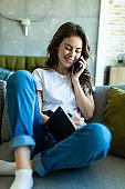 Young pretty woman doing paperwork and using mobile phone at home