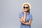 Young attractive hipster teen girl in sunglasses and straw hat isolated on white background